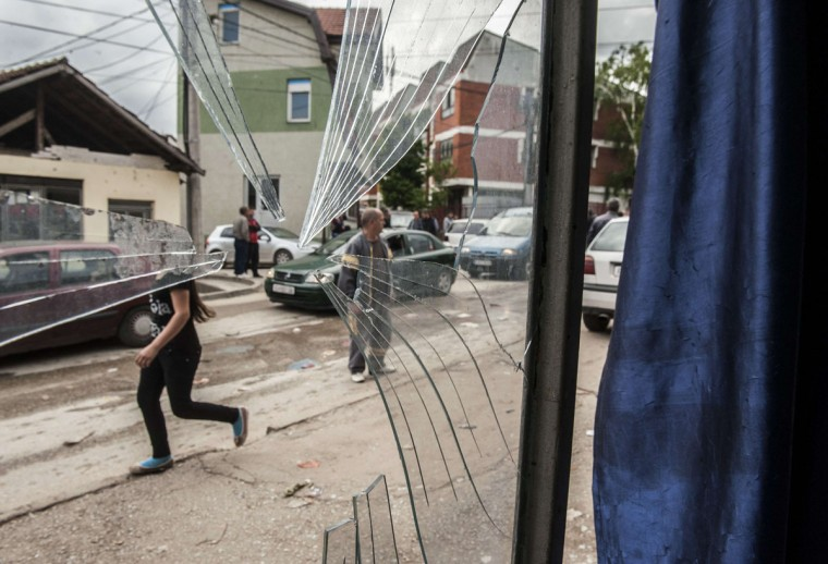 A girl walks next to a damaged shop after fighting between Macedonian police and an armed group in the town of Kumanovo on May 11, 2015. Shooting broke out for a second day on May 10 in northern Macedonia as concern mounted in Europe after clashes between police and unidentified gunmen that erupted on May 9 at dawn in the restive Balkan nation left at least six officers dead along with some 30 injured. (AFP Photo/P /armend )