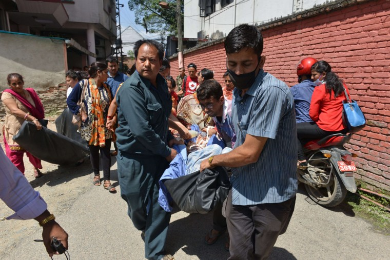 Nepalese patients are carried out of a hospital building as a 7.4 magnitude earthquake hits the country, in Kathmandu on May 12, 2015. A 7.4-magnitude earthquake hit devastated Nepal, sending terrified residents running into the streets in the capital Kathmandu, according to witnesses and the US Geological Survey. The quake struck at 12:35pm local time in the Himalayan nation some 83 kilometres (52 miles) east of Kathmandu, more than two weeks after a 7.8-magnitude quake which killed more than 8,000 people. (AFP Photo/Prakash Mathema)