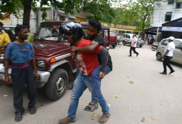 An Indian bystander carries an injured youth who fell downstairs at Siliguri Hospital as a tremor struck in Siliguri on May 12, 2015. A new earthquake of 7.3-magnitude and several powerful aftershocks hit devastated Nepal on May 12, killing at least four people and sending terrified residents running into the streets of the traumatised capital. The quake was felt as far away as New Delhi, and officials said it caused buildings to collapse in Chinese-controlled Tibet. (AFP Photo/Diptendu Dutta)