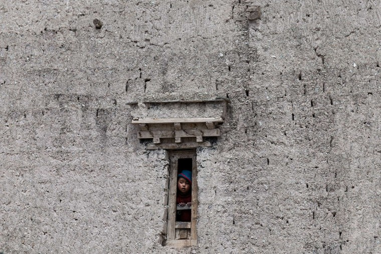 This photograph taken on May 9, 2015, shows a young Indian boy looking out of a window in Yurutse, in the Markha Valley in Ladakh. (Alex Ogle/AFP/Getty Images)