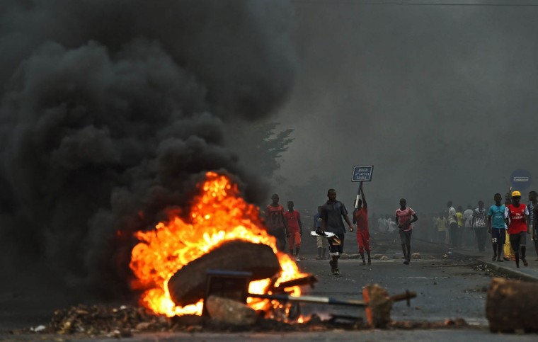 Protesters opposed to the Burundian president Pierre Nkurunziza's third term in office gather by a burning barricade during a demonstration in the Cibitoke neighborhood of Bujumbura on May 19, 2015. Thousands of demonstrators opposed to Burundian President Pierre Nkurunziza defied warning shots and took to the streets of Bujumbura, as their leaders called for them to overcome their fears and continue the fight. (Carl de Souza/Getty Images)
