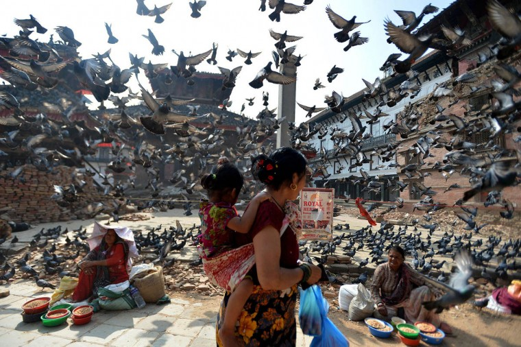 Flying pigeons pass over Nepalese street vendors near the earthquake damaged UNESCO World Heritage Site, Durbar Square in Kathmandu on May 20, 2015. Nearly 8,500 people have now been confirmed dead in the disaster, which destroyed more than half a million homes and left huge numbers of people without shelter with just weeks to go until the monsoon rains. (Ishara S. Kodikara/Getty Images)