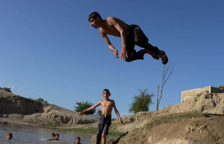 An Afghan youth dives into a ditch of muddy water to beat the heat on the outskirts of Jalalabad in Nangarhar province. (Noorullah Shirzada/Getty Images)