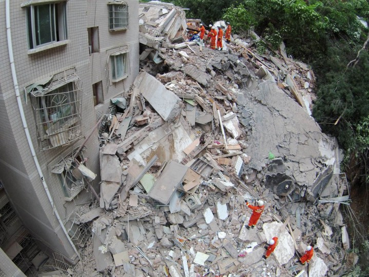 Rescuers look for survivors in the ruins of a collapsed nine story residential apartment in Guiyang, southwest China's Guizhou province on May 20, 2015. The collapse, triggered by a landslide on a nearby hill, has affected 35 households with the death toll still unknown, state media reported. (Getty Images)