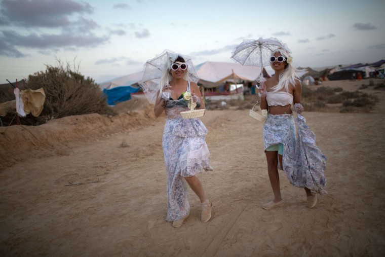 Women dressed in costumes walk with their umbrellas during the 2015 Midburn festival in the Negev Desert near the Israeli kibbutz of Sde Boker on May 21, 2015. (MENAHEM KAHANA/AFP/Getty Images)