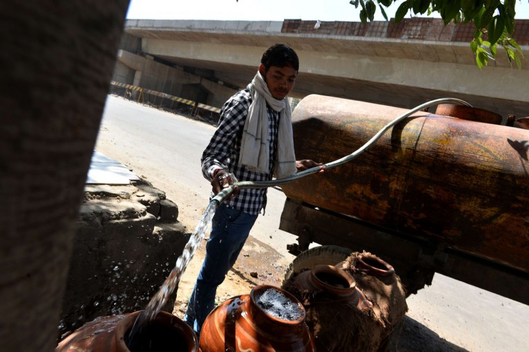 An Indian man fills a container with water from a tanker in Gurgaon on the outskirts of New Delhi on May 27, 2015. More than 1,100 people have died in a blistering heatwave sweeping India, authorities said May 27, 2015, as forecasters warned searing temperatures would continue. (Chandan Khanna/AFP/Getty Images)