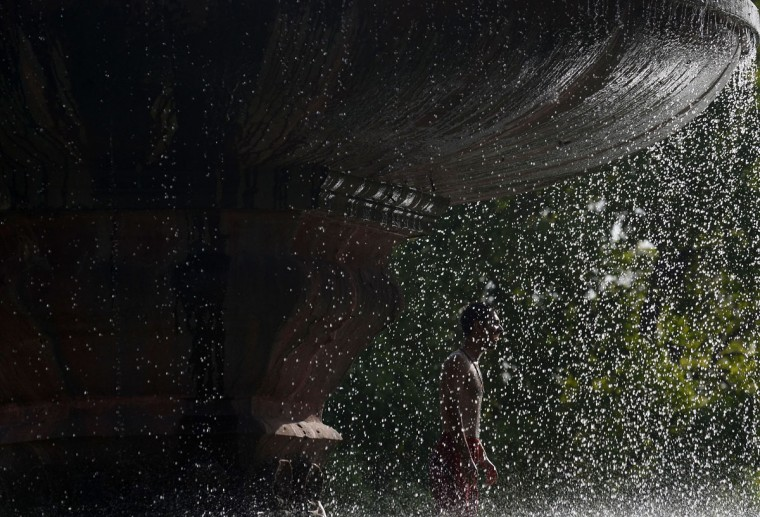 An Indian youth stands under a fountain near India Gate amid soaring temperatures in New Delhi on May 27, 2015. More than 1,100 people have died in a blistering heatwave sweeping India, authorities said May 27, 2015, as forecasters warned searing temperatures would continue. (Sajjad Hussein/AFP/Getty Images)