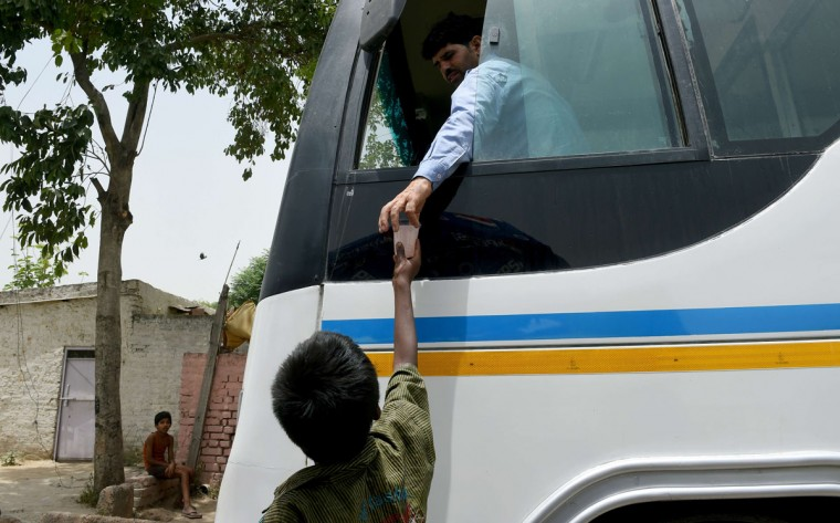 An Indian child hands over a glass of cold sweet water to a bus conductor on a hot afternoon in New Delhi on May 28, 2015. More than 1,100 people have died in a blistering heatwave sweeping India, authorities said, as forecasters warned searing temperatures would continue. (Money Sharma/AFP/Getty Images)