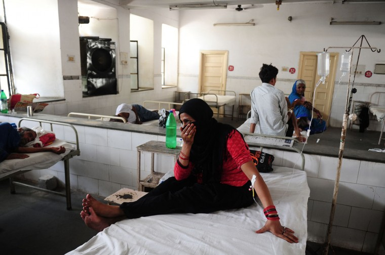 Indian diarrhoea patient Nansi Bano gestures as she sit on a bed in a government hospital in Allahabad on May 28, 2015, as scorching weather conditions continue across India. Hospitals in India were struggling to cope with an influx of victims of a blistering heatwave that has claimed nearly 1,500 lives in just over a week. (Sanjay Kanojia/AFP/Getty Images)