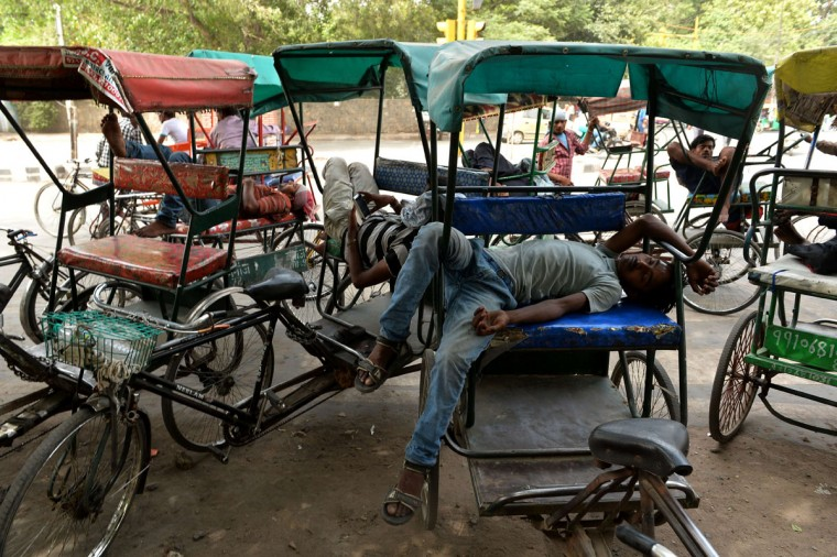 Indian cycle rickshaw riders sleep during the heat of the day in New Delhi on May 28, 2015. More than 1,100 people have died in a blistering heatwave sweeping India, authorities said, as forecasters warned searing temperatures would continue. (Chandan Khanna/AFP/Getty Images)