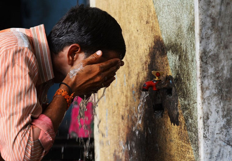 An Indian man washes his face at a roadside tap during rising temperatures in New Delhi on May 28, 2015. Hospitals in India battled May 28, 2015 to treat victims of a blistering heatwave that has claimed nearly 1,500 lives in just over a week -- the highest number recorded in two decades. (Sajjad Hussain/AFP/Getty Images)