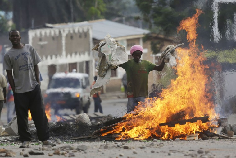 Protesters stand by a burning barricade in the Musaga neighborhood of Bujumbura, Burundi, Thursday May 21, 2015. Protests continue against the President's decision to seek a third term. (AP Photo/Jerome Delay)