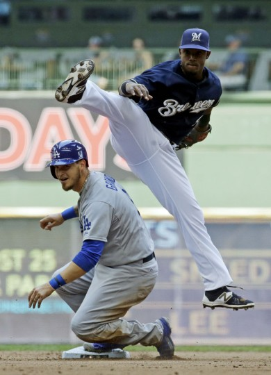 Milwaukee Brewers shortstop Jean Segura leaps over Los Angeles Dodgers' Yasmani Grandal to turn a double play on a ball hit by Adrian Gonzalez during the fifth inning of a baseball game Thursday, May 7, 2015, in Milwaukee. (AP Photo/Morry Gash)