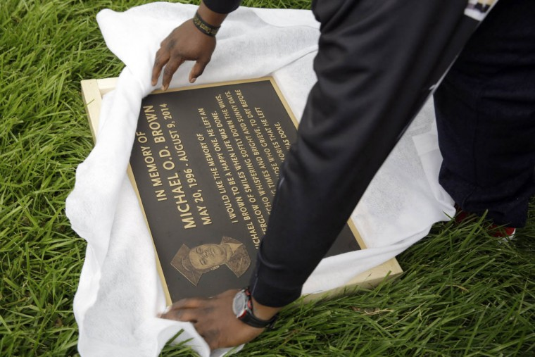 Michael Brown Sr. unwraps a plaque remembering his son, Michael Brown, to show volunteers as they remove items left at a makeshift memorial to Michael Brown Wednesday, May 20, 2015, in Ferguson, Mo. The memorial that has marked the place where Brown was fatally shot by a police officer in August has been removed and will be replaced with a permanent plaque. (AP Photo/Jeff Roberson)