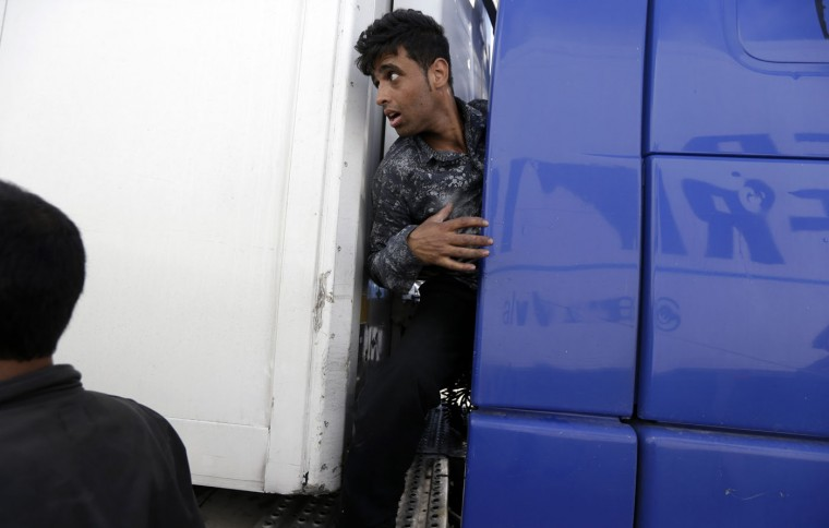 An Afghan migrant tries to hide on a truck traveling to Italy from the southern Greek city of Patras, Thursday, May 28, 2015. In an effort to help manage more than 80,000 people who have landed on European shores so far this year, mostly in Italy and Greece, the EU's executive Commission is proposing to relocate thousands of refugees to other member countries and wants to launch a security operation in the Mediterranean to eliminate the trafficking operations. (AP Photo/Thanassis Stavrakis)