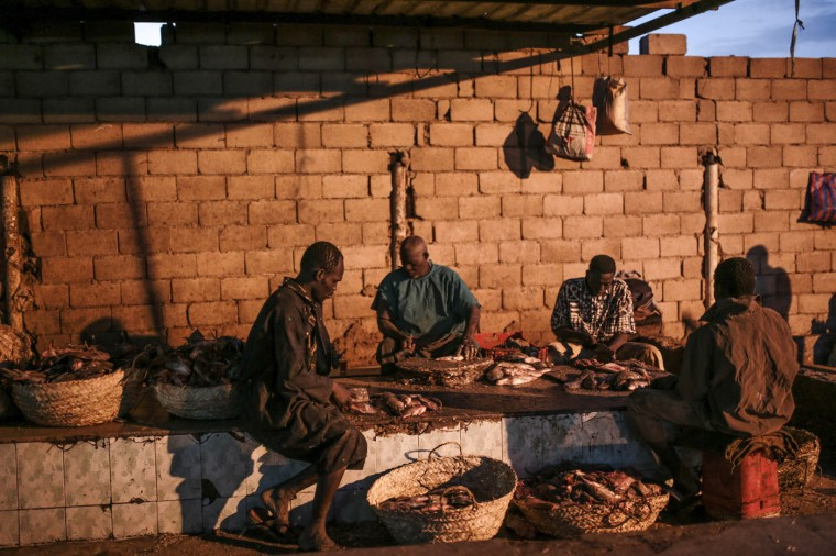 In this Thursday, April 16, 2015 photo, Sudanese fishermen clean fish before selling them at the Omdurman fish market, which operates before dawn until sunrise, in Khartoum, Sudan. (AP Photo/Mosa'ab Elshamy)