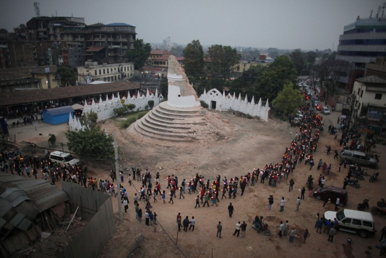 Nepalese people pay tributes to the victims of the April 25 earthquake, as they walk with lighted candles past the destroyed landmark Dharahara tower in Kathmandu, Nepal, Thursday, May 7, 2015. The quake killed thousands and injured many more as it flattened mountain villages and destroyed buildings and archaeological sites in Kathmandu. (AP Photo/Niranjan Shrestha)