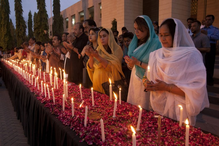 Pakistani lawmakers light candles and pray for the victims of a bus attack in Karachi, Pakistan, Thursday, May 14, 2015. Amid tight security, hundreds of Pakistanis Thursday paid their respects at a mass funeral for 45 minority Shiites who were killed in an attack on a bus in the southern city of Karachi. (AP Photo/Shakil Adil)