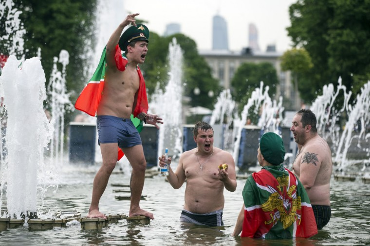 Russian border guard veterans with Russian Border guard flags gesture while bathing in a fountain in Moscow's Gorky Park as they celebrate Border Guards Day, in Moscow, Russia, Thursday, May 28, 2015. (AP Photo/Pavel Golovkin)