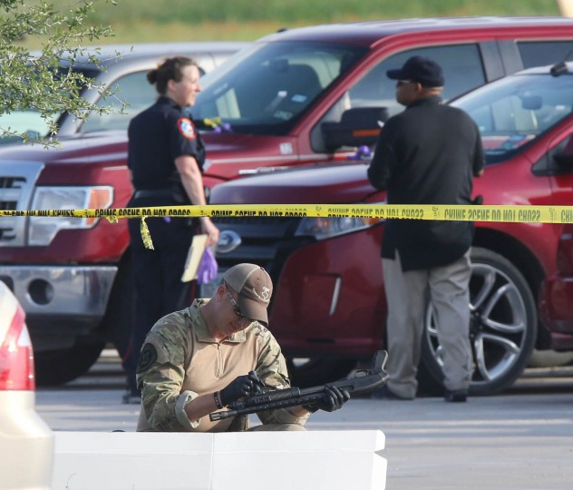 A police officer recovers a shotgun while sweeping through the parking lot of a Twin Peaks restaurant Tuesday, May, 19, 2015, in Waco, Texas. A deadly weekend shootout involving rival motorcycle gangs at the restaurant apparently began with a parking dispute and someone running over a gang member's foot, police said Tuesday. (Jerry Larson/Waco Tribune-Herald via AP)