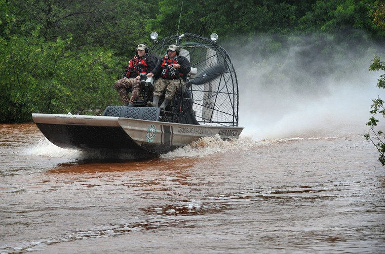 Palo Pinto County Game Wardens David Pelizarri, left, and Matt Waggoner test their air boat on the Wichita River in Wichita Falls, Texas Friday, May 22, 2015, near River Road. The Texas Parks and Wildlife has two jet boats, two prop boats and the air boat on stand-by if needed for water rescue duty during the area flooding. (AP Photo/Wichita Falls Times Record News, Torin Halsey)