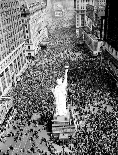 """People crowd Times Square at 42nd Street in New York City on May 8, 1945, as the V-E Day celebration continues into the night. The dim-out and the brownout of the """"Great White Way"""" have been replaced once more by the bright lights of victory following World War II. (AP Photo/Matty Zimmerman)"""