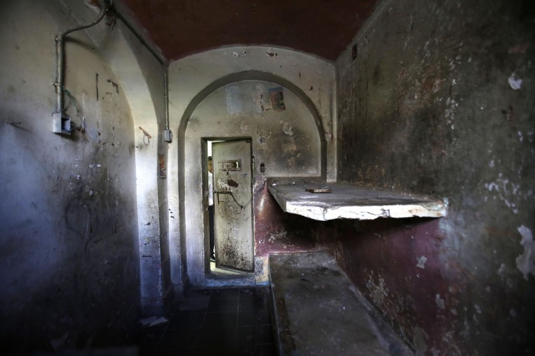 """In this April 7, 2015 photo, a tourist peers through the door of a jail cell inside the now empty Garcia Moreno prison during a guided tour for the public in Quito, Ecuador. According to tour guides, this cell was nicknamed """"Los Polillas,"""" or """"The Moths."""" Here, in a room designed to hold two prisoners, about 15 inmates with drug addictions were locked in overnight by the prison gangs that controlled daily life. The locked-in prisoners were also known to prostitute themselves to get access to drugs. (AP Photo/Dolores Ochoa)"""