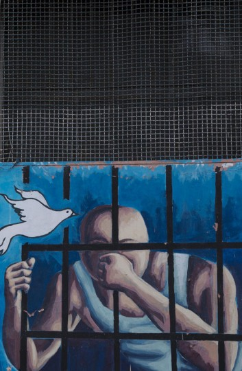This April 14, 2015 photo shows a mural of a prisoner behind bars and a flying dove on the wall inside a courtyard at the now empty Garcia Moreno Prison, during a guided tour for the public in Quito, Ecuador. Psychologist Oscar Ortiz, who worked with the inmates behind these walls, organized local artists to collaborate with the prisoners to adorn the walls with paintings. (AP Photo/Dolores Ochoa)