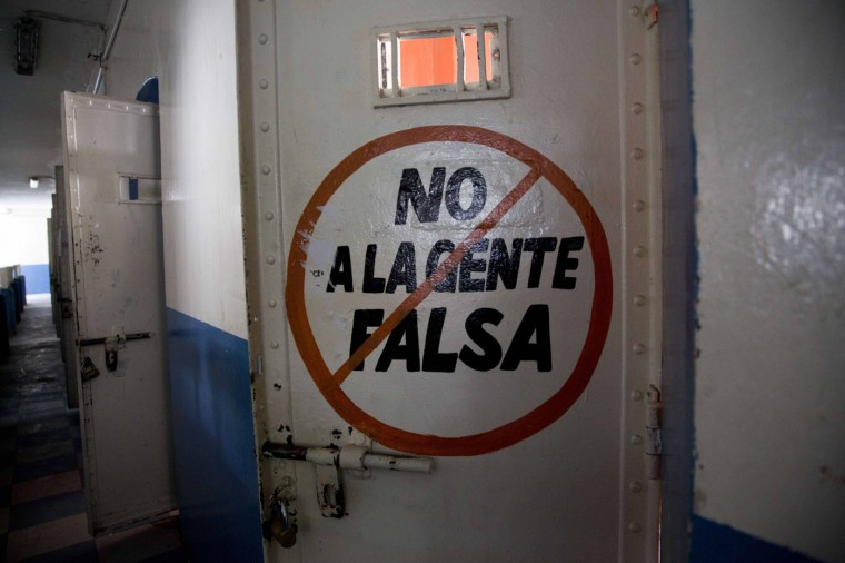 """This April 16, 2015 photo shows the exterior of a cell door covered with the message in Spanish: """"No to fake people"""" at the now empty Garcia Moreno Prison, during a guided tour for the public in Quito, Ecuador. Rich and poor, good and bad, innocent and guilty, inmates used the walls to record their days. (AP Photo/Dolores Ochoa)"""