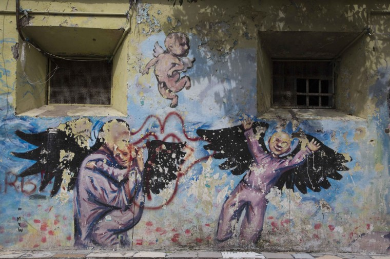 This April 16, 2015 photo shows a mural painted by inmates inside the courtyard of the now empty Garcia Moreno Prison, during a guided tour for the public in Quito, Ecuador. Psychologist Oscar Ortiz, who worked with the inmates behind these walls, organized local artists to collaborate with the prisoners to adorn the walls with paintings. (AP Photo/Dolores Ochoa)