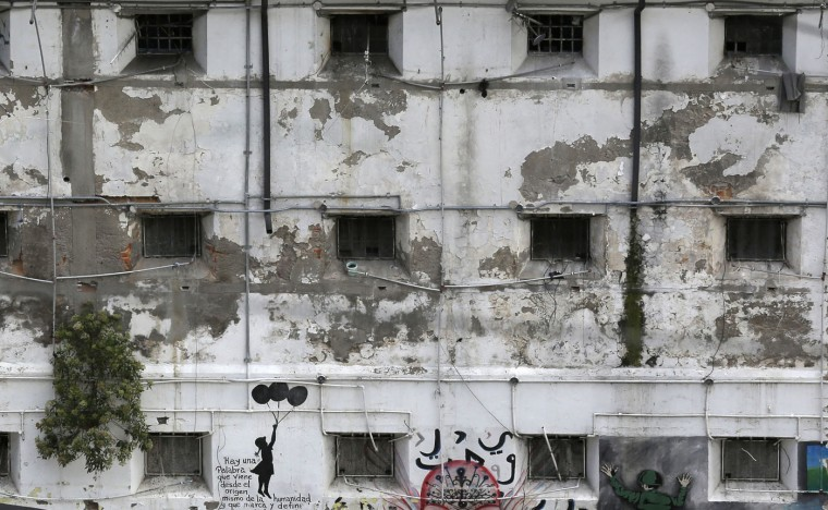 This April 9, 2015 photo shows prison cell windows facing an interior courtyard at the now empty Garcia Moreno Prison, during a guided tour for the public in Quito, Ecuador. The buildingís fate remains undecided, but authorities say one project being looked at would convert the old prison in the heart of the city into a luxury hotel. Another proposal would convert it into a city museum. (AP Photo/Dolores Ochoa)