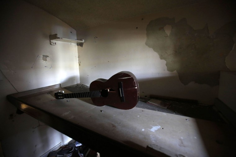 This April 9, 2015 photo shows a broken guitar left behind in a cell at the now empty Garcia Moreno Prison, during a guided tour for the public in Quito, Ecuador. Clothes, a guitar and other belongings were left behind by departing inmates who were transferred to a newer facility. (AP Photo/Dolores Ochoa)