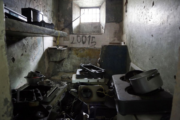 This April 9, 2015 photo shows a jail cell filled with cooking and electronic equipment left behind by prisoners being transferred from the Garcia Moreno Prison to a new facility, in Quito, Ecuador. Also left behind were rapidly scribbled phone numbers and written promises to never return to prison. (AP Photo/Dolores Ochoa)