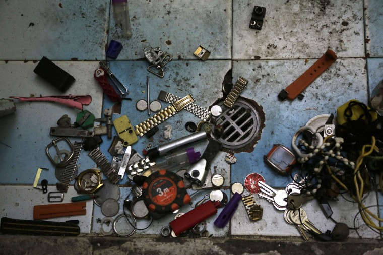 In this April 9, 2015 photo, personal items left behind by transferred prisoners lay by a bathroom floor drain inside a prison cell at the now empty Garcia Moreno Prison, during a guided tour for the public in Quito, Ecuador. Also left behind were cuttings from newspapers or magazines of pinup girls, clothing, instruments, and images of Jesus Christ. (AP Photo/Dolores Ochoa)