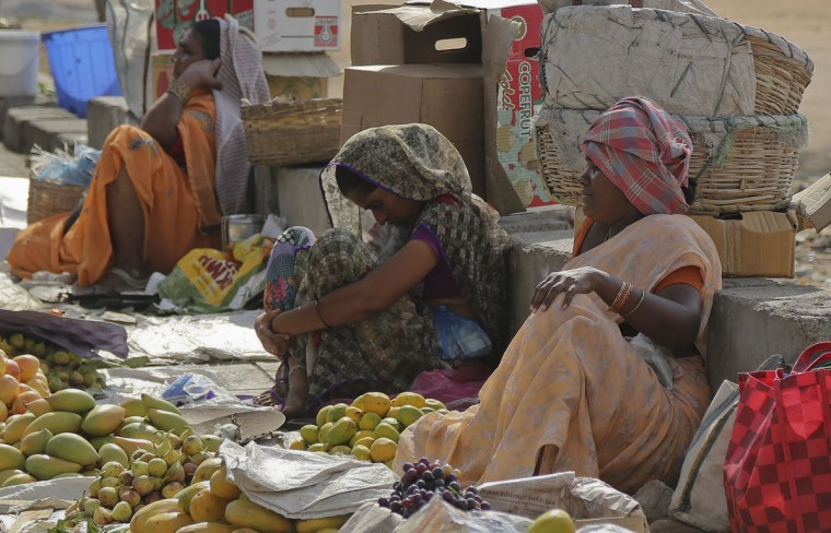 Indian fruit vendors wait for customers on a sidewalk in the shade of a tree on a hot summer day in Hyderabad, India, Thursday, May 28, 2015. Eating onions, lying in the shade and splashing into rivers, Indians were doing whatever they could Thursday to stay cool during a brutal heat wave that has killed more than 1,000 in the past month. (AP Photo/Mahesh Kumar A.)