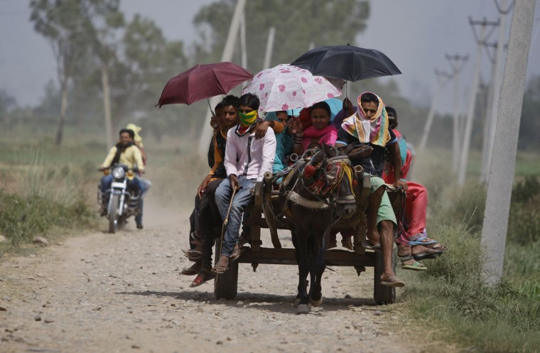 Indian devotees hold umbrellas to protect themselves from the sun during the annual festival of Sufi saint Saiwali Pir Baba at Sangral, near the India-Pakistan international border, about 38 kilometers south of Jammu, India, Thursday, May 28,2015. Eating onions, lying in the shade and splashing into rivers, Indians were doing whatever they could Thursday to stay cool during a brutal heat wave that has killed more than 1,000 in the past month. (AP Photo/Channi Anand)