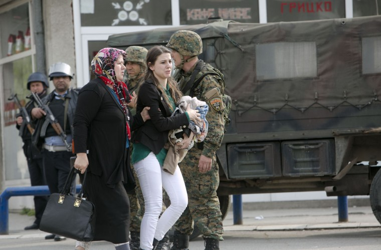 People are evacuated safely from the scene of an altercation involving the police, in northern Macedonian town of Kumanovo, on Saturday, May 9, 2015. Authorities in Macedonia say police have clashed with an armed terrorist group in this northern Macedonian town, and parts of the town have been sealed off. Macedonia's state-run news agency MIA reported that four police officers were injured by gunfire, and three of them were taken to a hospital in the capital, Skopje. (AP Photo/Visar Kryeziu)
