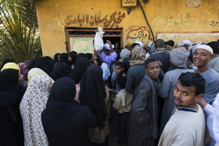 In this Tuesday, April 14, 2015 photo, women and men line up separately as they wait outside to buy bread at a bakery in a village near Abu al-Nasr, about 770 kilometers (480 miles) south of Cairo. Amira, the wife of Salama Osman who works in Cairo without his family most of the year, leaves her village house shortly after dawn everyday to buy bread at the shop. (AP Photo/Hiro Komae)
