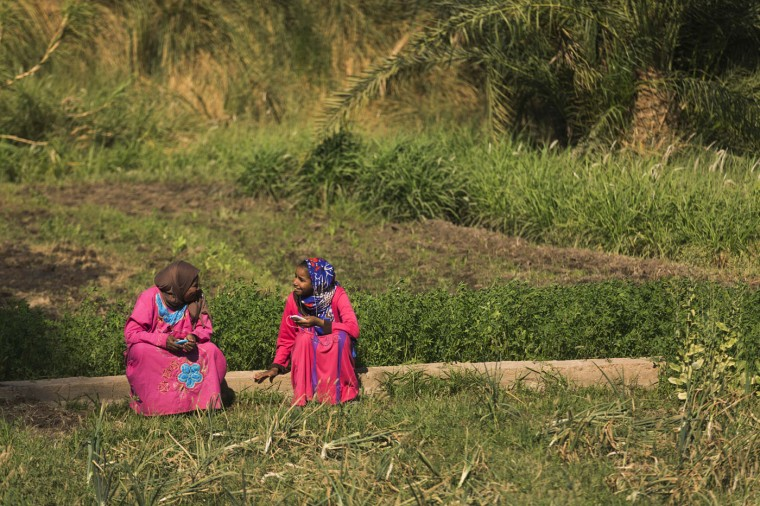 In this Friday, April 17, 2015 photo, Amira, wife of Salama Osman, and her daughter Ghada, talk about music playing on their cell phones while resting on the family plot of land, about 770 kilometers (480 miles) south of Cairo. Osman, 46, is on one of his two trips a year back home to the village, a rare respite from his hectic job back in the always-bustling Egyptian capital. (AP Photo/Hiro Komae)