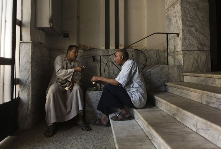 In this Tuesday, April 28, 2015 photo, Salama Osman, left, eats breakfast with Hagag Mohammed, a fellow doorman in his neighborhood, in the foyer to the apartment building where he works in Cairo, Egypt. Osman speaks every day by phone to his wife and children back in southern village of Abu Al-Nasr, but the money he makes in Cairo can support his wife, Amira, and his four children, forcing him to continue his migrant life in the big city. (AP Photo/Hiro Komae)