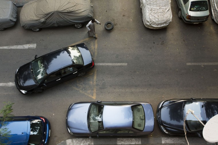 """In this Wednesday, April 29, 2015 photo, Salama Osman, a migrant from a southern village drops a tire to secure a parking place as a car drives off in front of the apartment building where he works, in Cairo, Egypt. Osman is a """"bawaab,"""" one of likely tens of thousands of migrant workers across Cairo who function as doormen, car parkers, errand runners, night watchmen, gardeners and just about anything. (AP Photo/Hiro Komae)"""