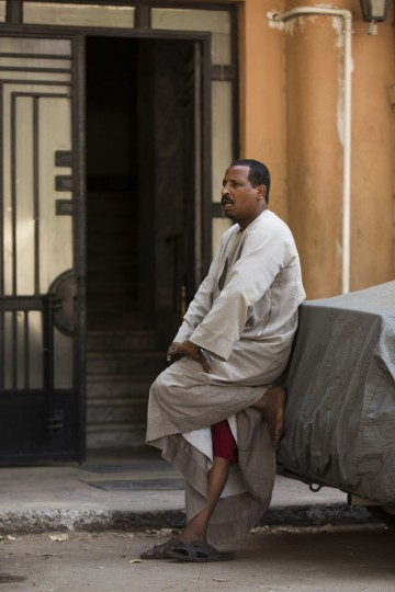 In this Tuesday, April 28, 2015 photo, doorman Salama Osman takes a break from his work, leaning against a car in front of the apartment building where he works in Cairo, Egypt. Osman speaks every day by phone to his wife and children back in southern village of Abu Al-Nasr, but the money he makes in Cairo can support his wife, Amira, and his four children, forcing him to continue his migrant life in the big city. (AP Photo/Hiro Komae)
