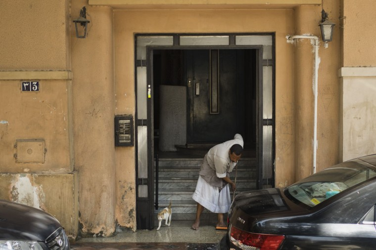 """In this Friday, May 1, 2015 photo, Salama Osman, a migrant from a southern village, cleans the entrance of his apartment building where he works in Cairo, Egypt. Osman is a """"bawaab,"""" one of likely tens of thousands of migrant workers across Cairo who function as doormen, car parkers, errand runners, night watchmen, gardeners and just about anything. His day begins before the tenants of his Cairo apartment building wake and ends only after the last returns home at night, a work week without weekends. (AP Photo/Hiro Komae)"""