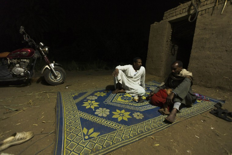 In this Friday, April 17, 2015 photo, Salama Osman, left, chats with his fisherman friend, Sayed Ahmed Abdoh, outside his home in Abu al-Nasr, about 770 kilometers (480 miles) south of Cairo. Osman, 46, is on one of his two trips a year back home where he can relax with his family, a rare respite from his hectic job back in the always-bustling Egyptian capital. (AP Photo/Hiro Komae)