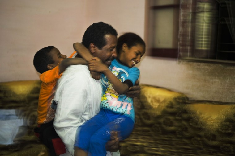 In this Friday, April 17, 2015 photo, Salama Osman, a migrant worker in Cairo, plays with his children Sameh, 5 1/2, left, and Zainab, 10, during a biannual trip back home in Abu al-Nasr, about 770 kilometers (480 miles) south of Cairo. Osman, 46, is on one of his two trips a year back home where he can relax with his family, a rare respite from his hectic job back in the always-bustling Egyptian capital. (AP Photo/Hiro Komae)