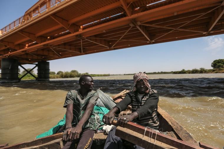 In this Wednesday, April 15, 2015 photo, Sudanese fishermen row their boat beneath Omdurman Bridge on the Nile River, in Khartoum, Sudan. (AP Photo/Mosa'ab Elshamy)