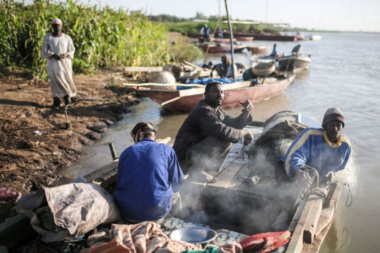 In this Wednesday, April 15, 2015 photo, Sudanese fishermen prepare prepare their boats on the banks of the Nile in the early morning hours in Omdurman, Khartoum, Sudan. The fishermen spend most of their days on the river; their four meter-long boats double up as temporarily homes. White awaiting a catch, the fishermen cook their meals onboard, listening to music playing from mobile phones which they charge with solar panels. (AP Photo/Mosa'ab Elshamy)