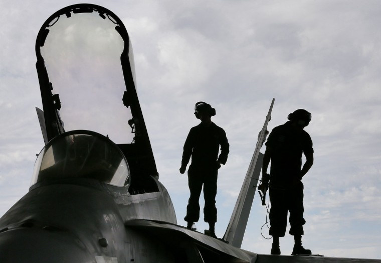 U.S. Marines work atop an F/A-18 at the 309th Aerospace Maintenance and Regeneration Group boneyard in Tucson, Ariz. on Thursday, May 21, 2015. The Marines are repairing F/A-18's to return to service at the 309th facility. (AP Photo/Matt York)