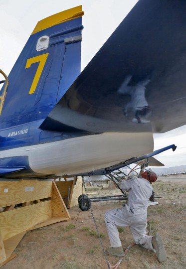 Preservation servicer Scott Carlson sprays a sealing paint on a former NAVY Blue Angel F-18 at the 309th Aerospace Maintenance and Regeneration Group boneyard, Thursday, May 21, 2015, in Tucson, Ariz. The 309th is the United States Air Forceís aircraft and missile storage and maintenance facility and provides long and short-term aircraft storage, parts reclamation and disposal. (AP Photo/Matt York)