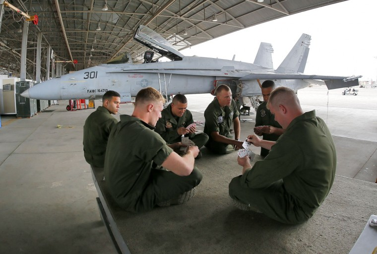 U.S. Marines play spades during a break at the 309th Aerospace Maintenance and Regeneration Group boneyard, Thursday, May 21, 2015, in Tucson, Ariz. The Marines are repairing F-A-18's to return to service at the 309th facility. (AP Photo/Matt York)
